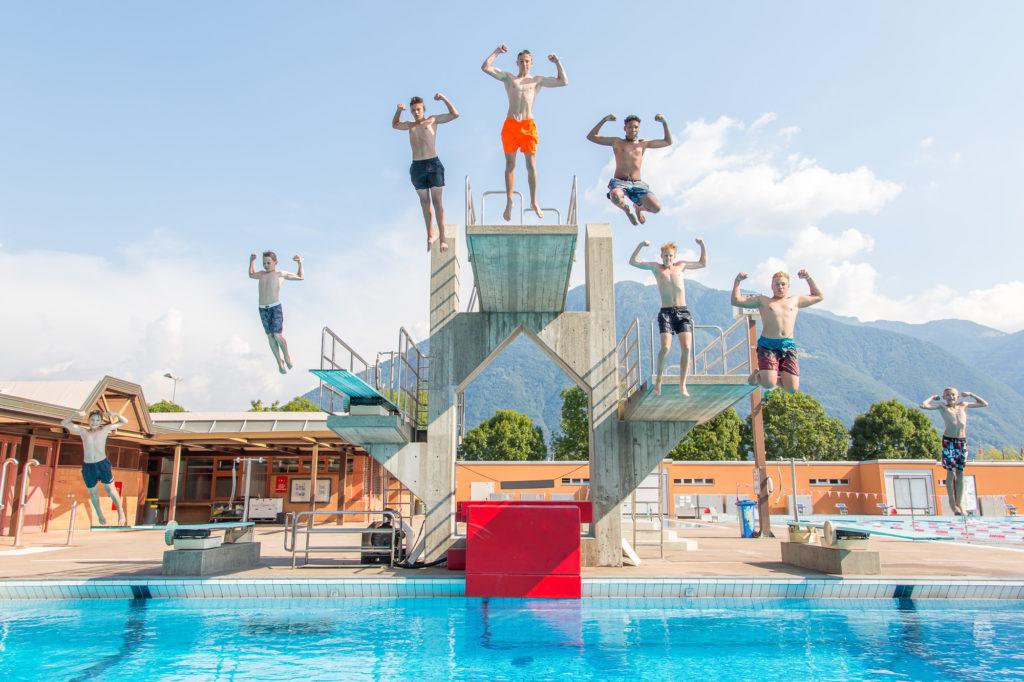 Acht Jungs springen gleichzeitig in derselben Pose von fünf verschiedenen Sprungbrettern ins Wasser
